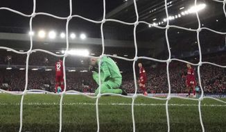 Liverpool's goalkeeper Adrian, bottom, reacts after fails to save the ball as Atletico Madrid's Marcos Llorente scores his side's second goal during a second leg, round of 16, Champions League soccer match between Liverpool and Atletico Madrid at Anfield stadium in Liverpool, England, Wednesday, March 11, 2020. (AP Photo/Jon Super)