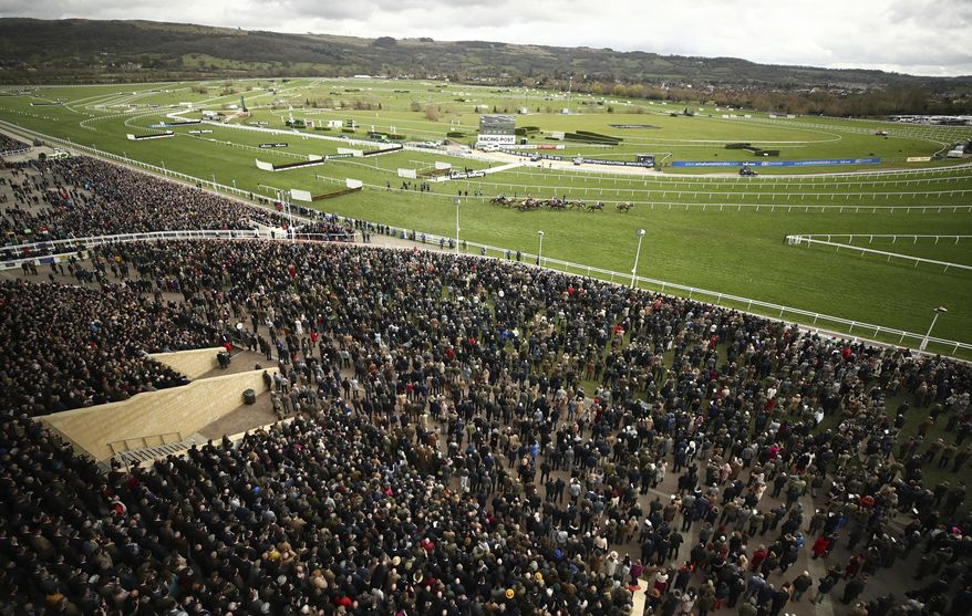 FILE - In this Wednesday March 11, 2020 file photo, a general view from the Grand Stand of the Ballymore Novices' Hurdle the Cheltenham Horse Racing Festival at Cheltenham Racecourse, England. Cheltenham Festival organisers have defended their decision to go ahead with the meeting last month after fears were raised that the mass gathering of people for the annual horse racing event helped spread coronavirus more widely around Britain. (Tim Goode/PA via AP, File)