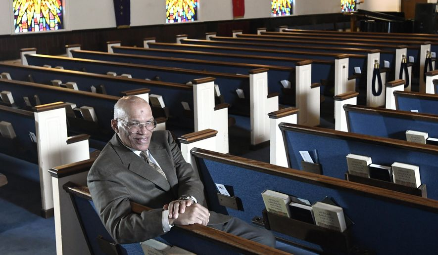In this Thursday, March 19, 2020, file photo, the Rev. Alvin J. Gwynn Sr., of Friendship Baptist Church in Baltimore, sits for a portrait in his church. Gwynn said that police tried to halt services at his church on Sunday, March 29, 2020, even though he had limited in-person attendance to 10 people. (AP Photo/Steve Ruark)