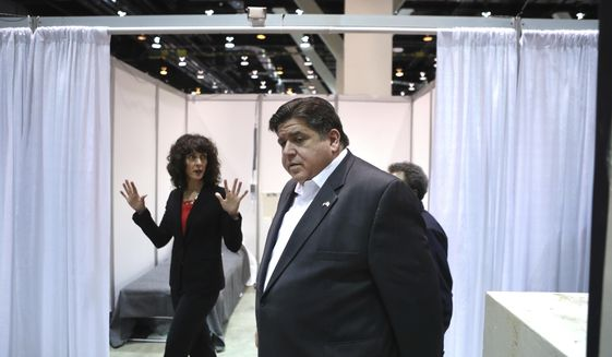 Illinois Gov. J.B. Pritzker tours Hall C Unit 1 of the COVID-19 alternate site at McCormick Place in Chicago on Friday, April 3, 2020. Hall C is planned to have 500 beds. In the background is Christina Bratis, clinical chief of staff of the facility. (Chris Sweda/Chicago Tribune via AP, Pool)