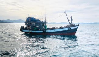 In this handout photo released on Sunday, April 5, 2020 by the Malaysian Maritime Enforcement Agency shows a wooden boat carrying suspected Rohingya migrants detained in Malaysian territorial waters off the island of Langkawi, Malaysia. Malaysian authorities said they have arrested a boatload of 202 people believed to be minority Muslim Rohingya refugees after their boat was found adrift Sunday morning near the northern resort island of Langkawi. (Malaysian Maritime Enforcement Agency via AP)