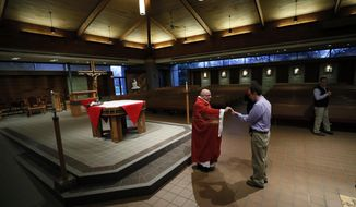 The Rev. Michael Amadeo, left, gives Holy Communion during the broadcast and recording of the Palm Sunday Mass at Our Lady's Immaculate Heart Catholic Church for parishioners to watch online Saturday, April 4, 2020, in Ankeny, Iowa. Sunday Masses continue to be available online in response to the new coronavirus outbreak. (AP Photo/Charlie Neibergall)