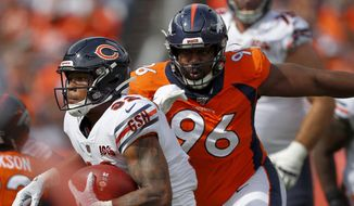 In this Sept. 15, 2019, file photo, Chicago Bears running back David Montgomery (32) is pursued by Denver Broncos defensive tackle Shelby Harris (96) during the first half of an NFL football game in Denver. The coronavirus pandemic has forced NFL teams to make free agent decisions without the benefit of meeting players face to face. That suppressed the market for plenty of lower-tier free agents such as Harris who signed a one-year deal for $2.5 million with a chance to earn another $750,000. (AP Photo/David Zalubowski, File) **FILE**