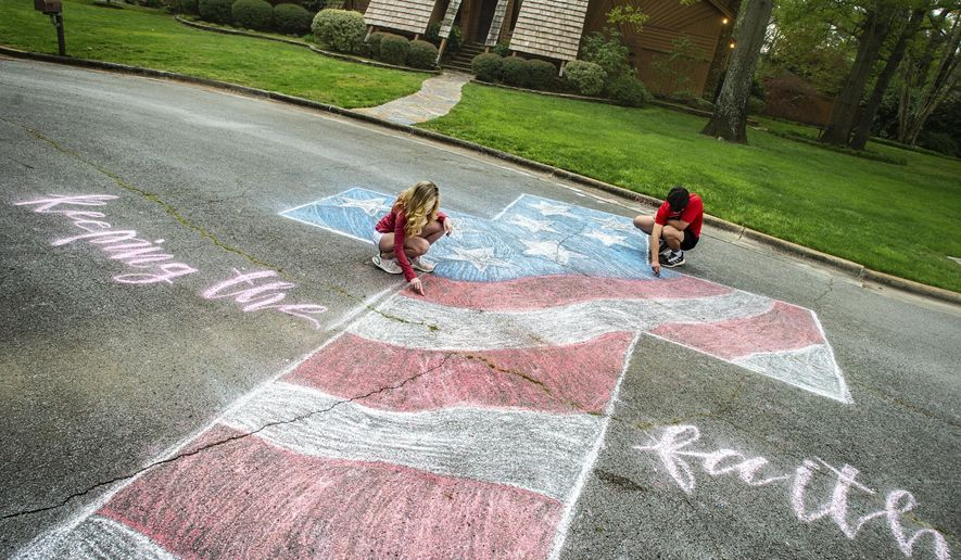 Layne Bjornseth, left, and her boyfriend Ben Glover touch up a mural with chalk off Southampton Court on Monday, March 30, 2020, in Decatur, Ala. Bjornseth's inspiration for the artwork is to share a message of hope and encouragement the coronavirus pandemic.  (Dan Busey/The Decatur Daily via AP)