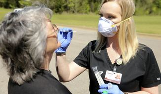 In this Thursday, April 2, 2020 photo, Shannon Bates, a nurse at Ripley Health Care Associates, demonstrates a COVID-19 test kit being given to Pattie Medlin, of Blue Mountain, in Ripley, Miss. (Adam Robison/The Northeast Mississippi Daily Journal via AP)