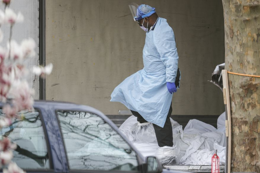 Medical workers step over bodies as they search a refrigerated trailer while wearing personal protective equipment due to COVID-19 concerns at Kingsbrook Jewish Medical Center, Friday, April 3, 2020, in the Brooklyn borough of New York. (AP Photo/John Minchillo)