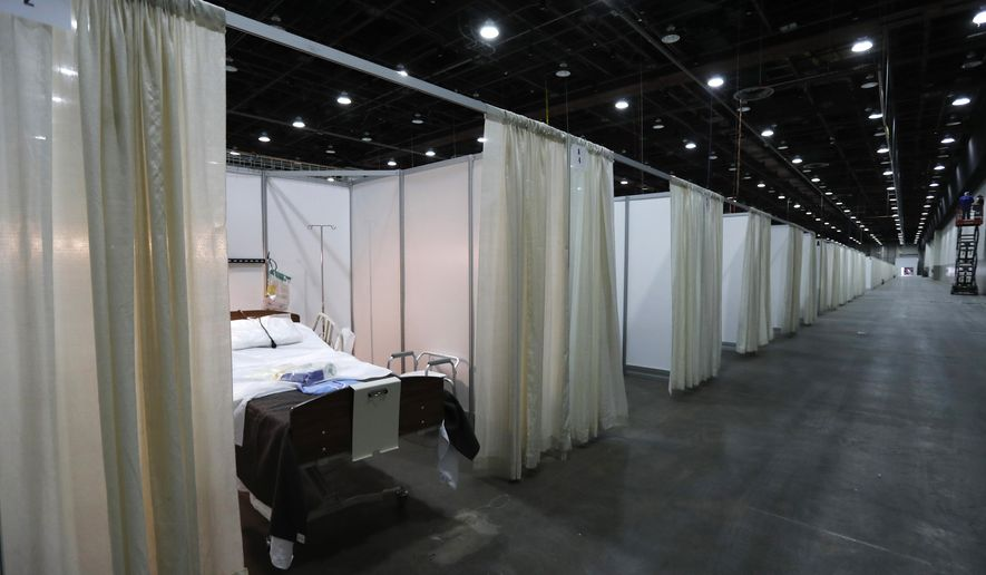 This photo shows a hospital bed in one of the temporary rooms at the TCF Center, Monday, April 6, 2020, in Detroit. The city's convention center was converted to accommodate an overflow of patients with the coronavirus. The U.S. Army Corps of Engineers began construction at the TCF Center to create a quarantined hospital setting with 1,000 beds as the pandemic spreads rapidly in the city. (AP Photo/Carlos Osorio)