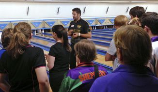 In this April 20, 2013 photo, Australian pro bowler Jason Belmonte, center, gives instructions during a clinic on the Sunshine Coast, Australia. Belmonte's return to Australia from another banner season on the PBA Tour in the United States was never going to be easy due to a logjam of Australians trying to return Down Under because of the coronavirus shutdown. (AP Photo/Dennis Passa)