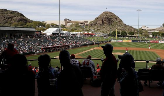 Fans watch a spring training baseball game between the Los Angeles Angels and the San Diego Padres, Thursday, Feb. 27, 2020, in Tempe, Ariz. (AP Photo/Darron Cummings)  **FILE**