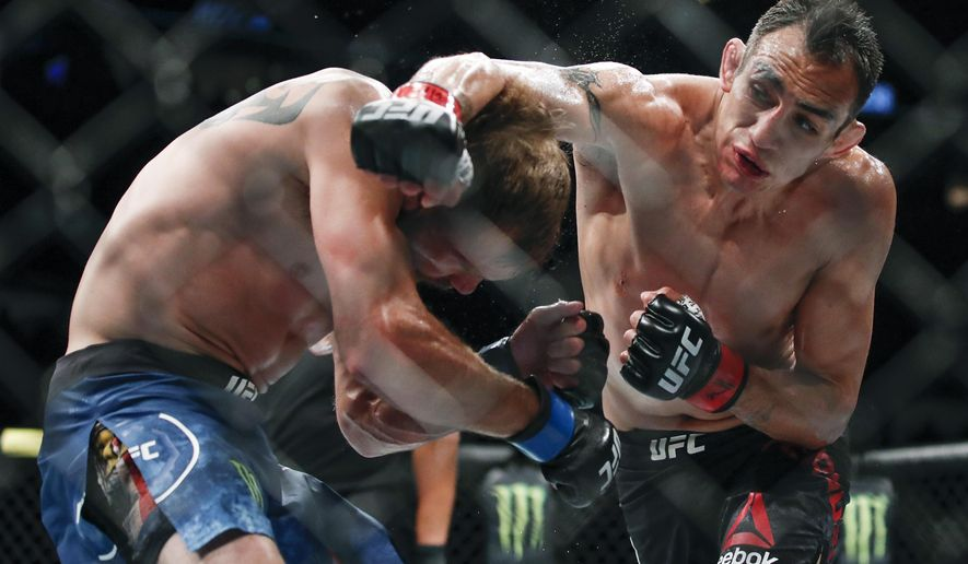 FILE - In this June 8, 2019, file photo, Tony Ferguson, right, punches Donald Cerrone, left, during their lightweight mixed martial arts bout at UFC 238 in Chicago. The UFC says Ferguson will fight Justin Gaethje for the interim lightweight title in the main event of UFC 249 on April 18, 2020. The mixed martial arts promotion announced the matchup Monday, April 6, 2020. Gaethje replaces lightweight champ Khabib Nurmagomedov, who is apparently unable to leave Russia during the coronavirus pandemic. (AP Photo/Kamil Krzaczynski, File)