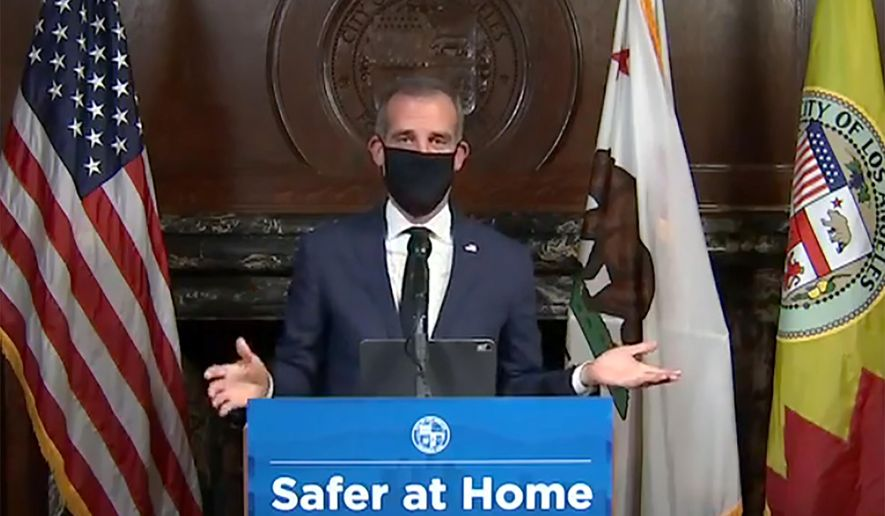 FILE - This Wednesday, April 1, 2020 file photo from a live stream video provided by the Office of Mayor Eric Garcetti shows Los Angeles Mayor Garcetti wearing a protective face mask during his daily coronavirus news conference in Los Angeles. Garcetti is currently conducting all briefings and interviews remotely. On Monday, April 6, 2020 Garcetti discussed the COVID-19 outbreak in a telephone interview with The Associated Press. Garcetti is encouraged by a slowing rate of corornavirus infections but the city is preparing for potentially tougher restrictions if the numbers take a turn for the worse. (Office of Mayor Eric Garcetti via AP, File)