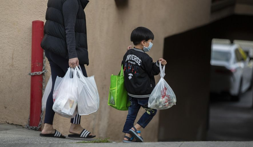 FILE - In this April 2, 2020 file photo, an adult and a child, both wearing face masks amid the coronavirus outbreak, carry bags in the Chinatown neighborhood of Los Angeles. The first U.S. national data on COVID-19 in children suggest that while the virus usually isn't severe in kids, some do get sick enough to require hospital treatment. The new information is in a federal Centers for Disease Control and Prevention report released Monday, April 6, 2020. (AP Photo/Damian Dovarganes, File)