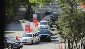 A line of cars gather to enter a COVID-19 testing site on Georgia Tech's campus, Monday, April 6, 2020, in Atlanta. (AP Photo/Brynn Anderson)