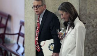 FILE - In this March 26, 2020, file photo Ohio Gov. Mike DeWine, left, and Dr. Amy Acton, director of the Ohio Department of Health, leave the State Room before their daily update on the states response to the ongoing COVID-19 pandemic at the Ohio Statehouse in Columbus, Ohio. (Joshua A. Bickel/The Columbus Dispatch via AP, File)