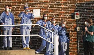 Hospital workers appear at a staff entrance as motorcyclists and friends of Chad Edmonds, of Cedar Rapids, wave from a parking ramp on the UnityPoint St. Luke's campus in Cedar Rapids, Iowa, on Sunday, April 5, 2020. Edmonds has been battling COVID-19, the disease caused by the new coronavirus, in the hospital and is in an induced coma, according to his parents, who took part in the show of support. (Rebecca F. Miller/The Gazette via AP)