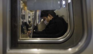 A man naps in a train Monday, April 6, 2020, in Tokyo. Reports say Prime Minister Shinzo Abe plans to declare an emergency in Tokyo and other cities Tuesday. (AP Photo/Jae C. Hong)