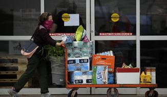 A woman wearing a mask exits a Costco store with her purchases Monday, April 6, 2020 in Lenexa, Kan. Shoppers continue to stock up on basic supplies while stores are adopting occupancy restrictions, plexiglass shields, one-way isles and other measures in hopes of stemming the spread of the new coronavirus. (AP Photo/Charlie Riedel)