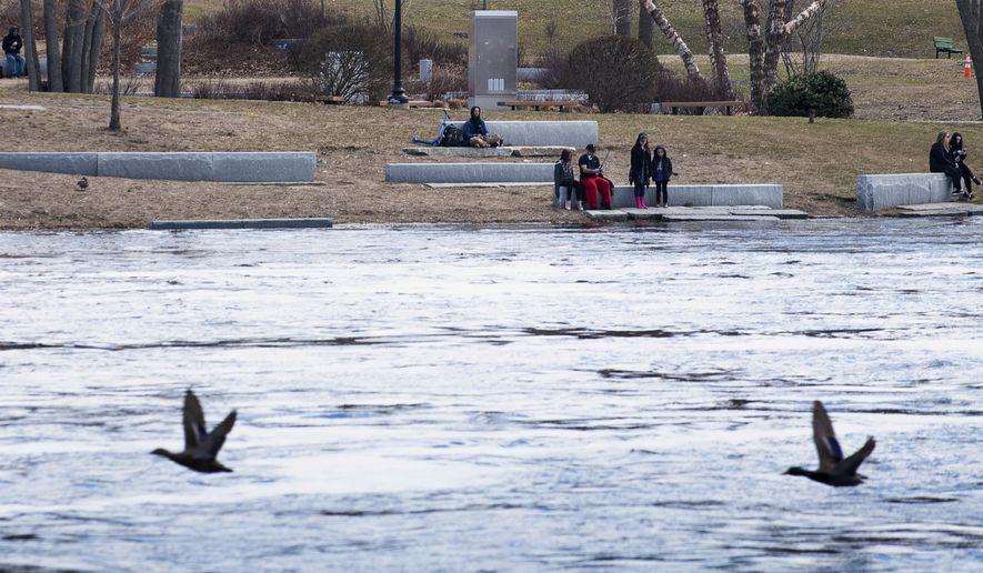 People enjoy the beautiful weather in Simard Payne Memorial Park in Lewiston, Maine, Saturday, April 4, 2020. (Russ Dillingham/Sun Journal via AP)