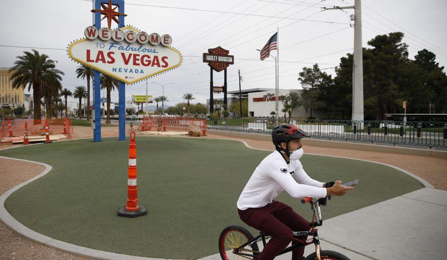 "A man wearing a mask amid the coronavirus outbreak rides a bike near the ""Welcome to Fabulous Las Vegas Nevada"" sign along the Las Vegas Strip, Monday, April 6, 2020, in Las Vegas. (AP Photo/John Locher)"