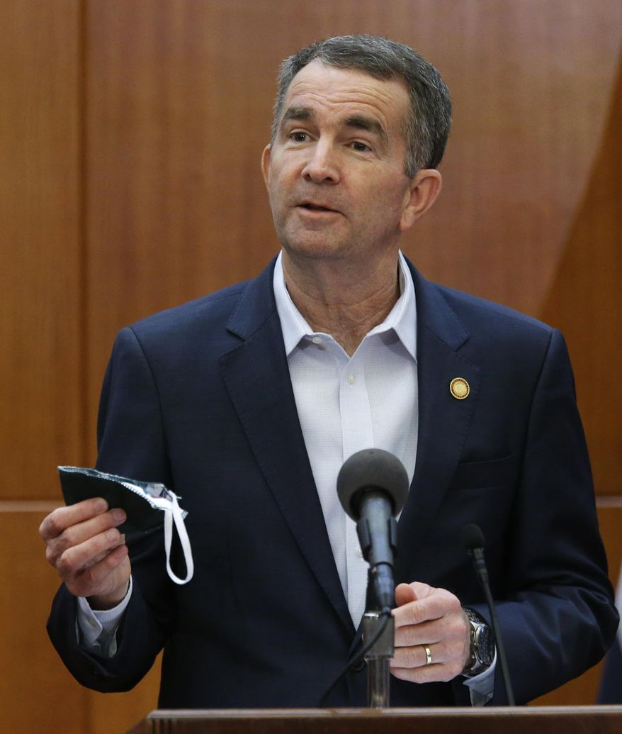 Virginia Gov. Ralph Northam holds up a face mask he carries to help prevent the spread of the coronavirus as he addresses his daily news briefing inside the Patrick Henry Building in Richmond, Va., Monday, April 6, 2020. He said that the mask was made by inmates at one of Virginia's penal facilities. (Bob Brown/Richmond Times-Dispatch via AP)