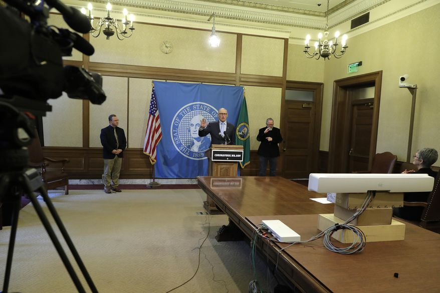 Washington Gov. Jay Inslee, center, speaks at a news conference Monday, April 6, 2020, at the Capitol in Olympia, Wash. as state schools Superintendent Chris Reykdal looks on at left. Inslee announced Monday that schools will remain physically closed for the remainder of the school year due to the coronavirus outbreak, and that public and private school students will continue distance learning through June. (AP Photo/Ted S. Warren)