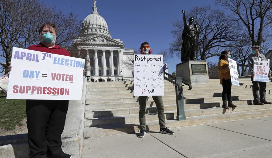 A group with C.O.V.I.D., Citizens Outraged Voters in Danger, protest wearing masks outside the State Capitol during a special session regarding the spring election in Madison, Wis., Saturday, April 4, 2020. (Amber Arnold/Wisconsin State Journal via AP)