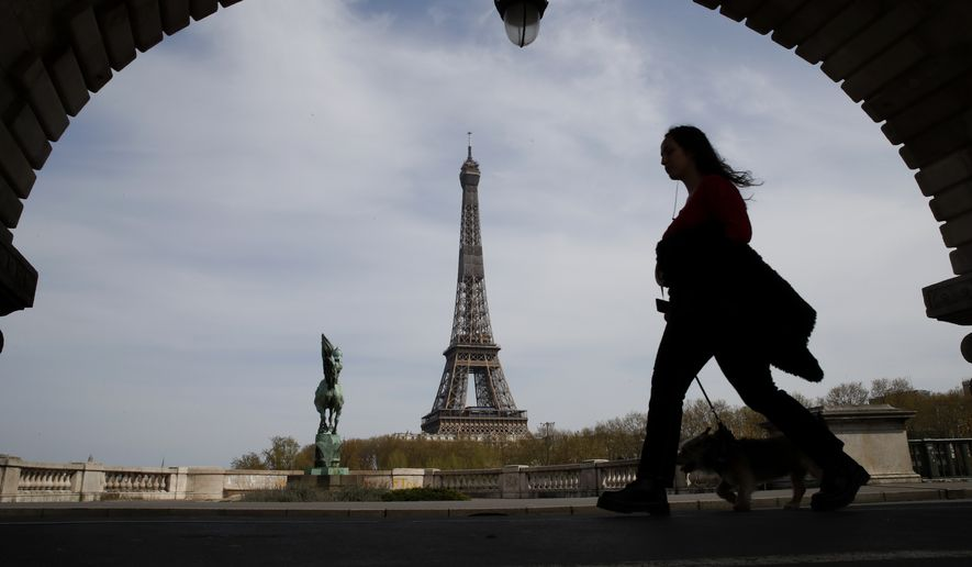A woman walks her dog on a Paris bridge, with the Eiffel Tower seen in the background, during a nationwide confinement to counter the COVID-19, Tuesday, April 7, 2020. The new coronavirus causes mild or moderate symptoms for most people, but for some, especially older adults and people with existing health problems, it can cause more severe illness or death. (AP Photo/Christophe Ena)