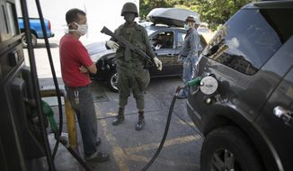 Soldiers loyal to Venezuelan President Nicolas Maduro are guarding gas stations as lines get longer amid a reduction in oil production. (Associated Press)