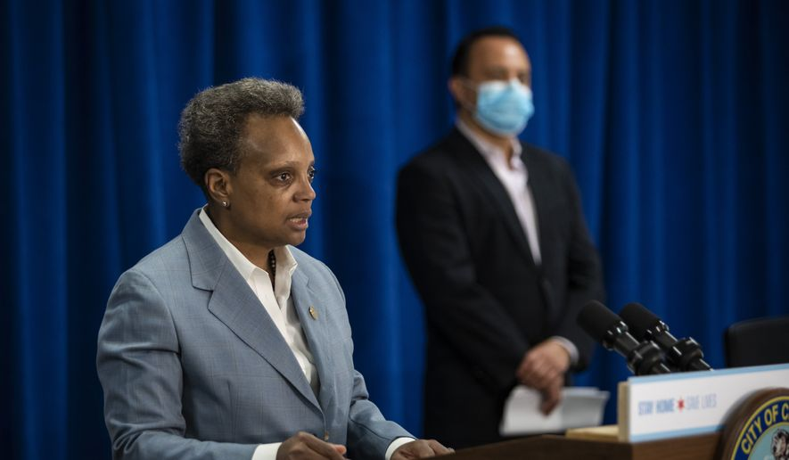 Chicago Mayor Lori Lightfoot speaks, as Alderman George Cardenas looks on during a press conference at City Hall, Tuesday morning, April 7, 2020, in Chicago. Chicago immigrants who do not have legal status in the U.S. are eligible for all relief programs run by the city amid the coronavirus outbreak, Mayor Lightfoot ordered Tuesday.  (Ashlee Rezin Garcia/Chicago Sun-Times via AP)