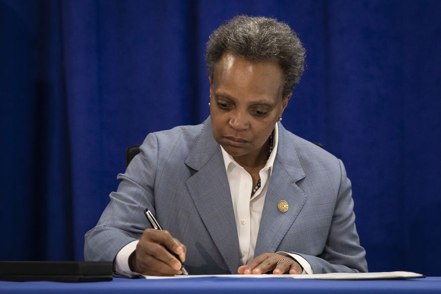 Chicago Mayor Lori Lightfoot signs an executive order to ensure coronavirus-related benefits offered by the city of Chicago are available to immigrants and refugees, Tuesday morning, April 7, 2020. (Ashlee Rezin Garcia/Chicago Sun-Times via AP)