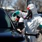 A biohazard cleaner wearing personal protective equipment applies cleaner to a police car, Monday, April 6, 2020, in Wheat Ridge, Colo., as police vehicles are disinfected to protect officers from the new coronavirus as a statewide stay-at-home order remains in effect in an effort to reduce the spread of the virus. (AP Photo/David Zalubowski)