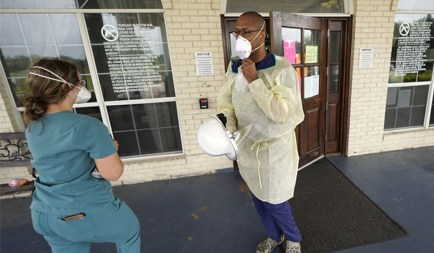 Dr. Robin Armstrong, right, adjusts his mask outside the entrance to The Resort at Texas City nursing home, where he is the medical director, Tuesday, April 7, 2020, in Texas City, Texas. Armstrong is treating nearly 30 residents of the nursing home with the anti-malaria drug hydroxychloroquine, which is unproven against COVID-19 even as President Donald Trump heavily promotes it as a possible treatment. Armstrong said Trump's championing of the drug is giving doctors more access to try it on coronavirus patients. More than 80 residents and workers have tested positive for coronavirus at the nursing home. (AP Photo/David J. Phillip)