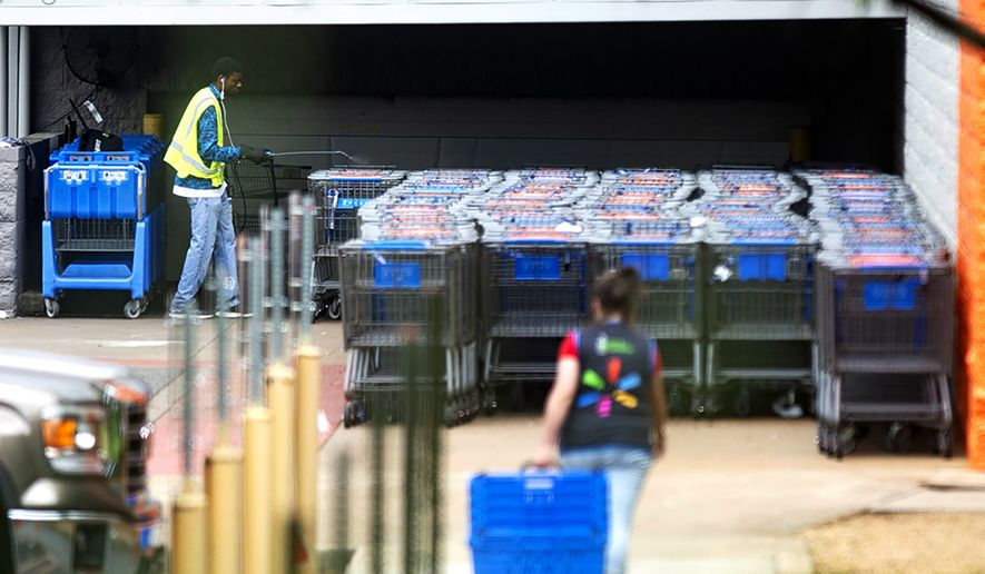 A Walmart employee sprays disinfectant on returned shopping carts Tuesday, April 7, 2020, in Nacogdoches, Texas. (Tim Monzingo/The Daily Sentinel via AP)