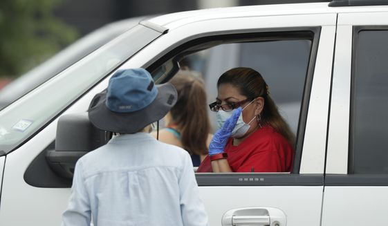 A woman sits in her car as workers and volunteers load her car with food at a San Antonio Food Bank drive-through distribution in San Antonio, Tuesday, April 7, 2020. The new coronavirus causes mild or moderate symptoms for most people, but for some, especially older adults and people with existing health problems, it can cause more severe illness or death. (AP Photo/Eric Gay) **FILE**