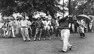 FILE - In this April 12, 1954, file photo, Sam Snead, White Sulphur Springs, W. Va., tees off in an 18-hole Masters playoff at Augusta National Golf Club in Augusta, Ga. Snead and Ben Hogan, standing behind, second from left, tied the day before in the championship.  In what was voted the sixth-best Masters, Snead won his third green jacket. (AP Photo/File)