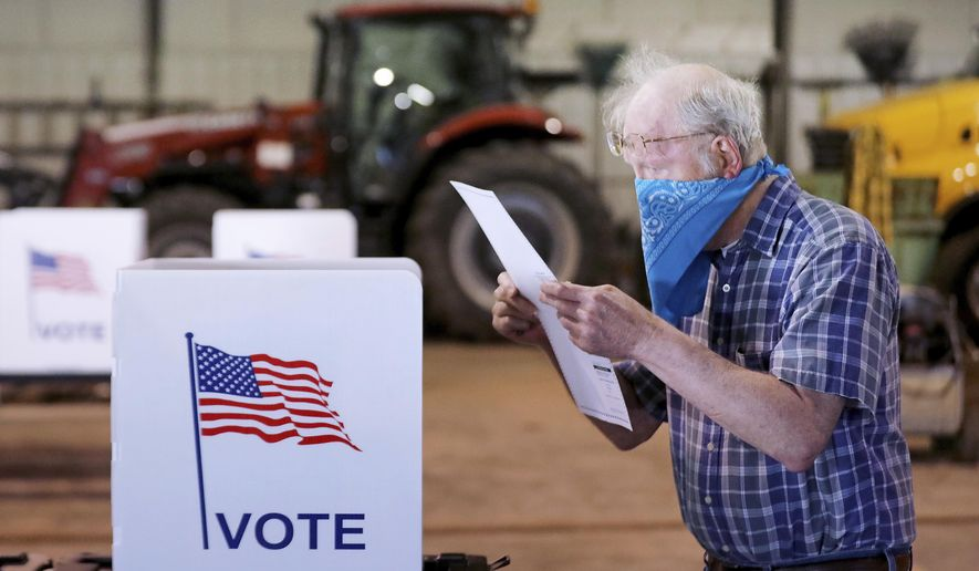 In this file photo, a voter reviews his selections on his ballot while voting at the town's highway garage building Tuesday, April 7, 2020 in Dunn, Wis.  (John Hart/Wisconsin State Journal via AP) **FILE**