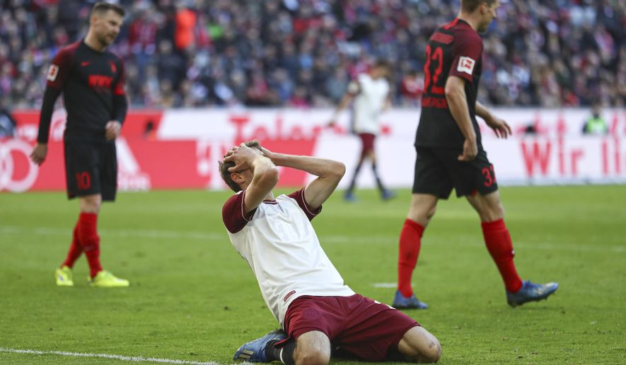 Bayern's Thomas Mueller covers his face after missing an opportunity to score during the German Bundesliga soccer match between FC Bayern Munich and FC Augsburg in Munich, Germany, Sunday, March 8, 2020. (AP Photo/Matthias Schrader)