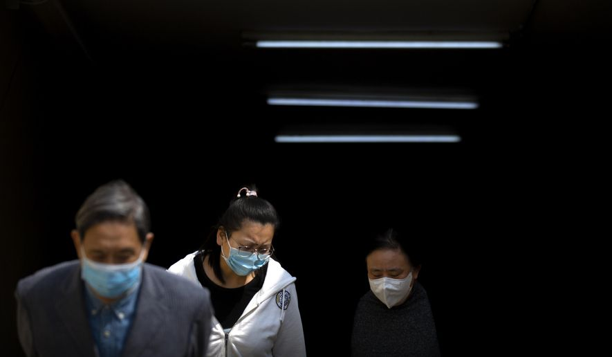 People wear face masks as they exit a subway station in Beijing, Tuesday, April 7, 2020. China on Tuesday reported no new deaths from the coronarivus over the past 24 hours and just 32 new cases, all from people who returned from overseas. (AP Photo/Mark Schiefelbein)