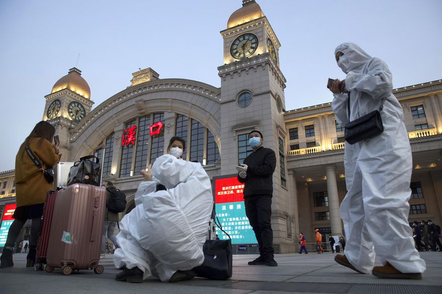 Passengers wearing protective suits to protect against the spread of new coronavirus gather outside of Hankou train station ahead of the resumption of train services in Wuhan in central China's Hubei Province, Wednesday, April 8, 2020. After 11 weeks of lockdown, the first train departed Wednesday morning from a re-opened Wuhan, the origin point for the coronavirus pandemic, as residents once again were allowed to travel in and out of the sprawling central Chinese city. (AP Photo/Ng Han Guan)