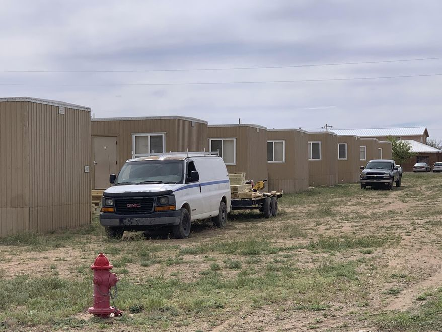 This Monday, April 6, 2020 photo, shows portable housing being erected in Columbus, N.M., for workers who are building a section of the U.S.-Mexico border wall. Immigrant advocates, some village residents and others are raising concerns about the influx of workers from elsewhere given the coronavirus pandemic. (Ray Trejo via AP)