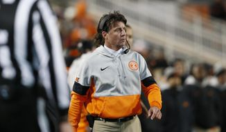 In this Nov. 30, 2019 file photo Oklahoma State head coach Mike Gundy walks on the sidelines during an NCAA college football game against Oklahoma in Stillwater, Okla. Gundy said Tuesday, April 7, 2020 he hopes to have his team return to its facilities on May 1, a proposed timetable that would defy federal social-distancing guidelines and was quickly disputed by the university and its athletic director. (AP Photo/Sue Ogrocki)  **FILE**
