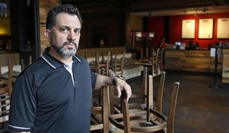 JJ Kuhn, general manager of Yucatan Taco Stand Tequilla Bar and Grill, poses for a photo in the empty dining room at the restaurant Friday, March 27, 2020, in Oklahoma City. The Women's College World Series, cancelled because of the COVID-19 outbreak, has been hosted in Oklahoma City every year except one since 1990. . (AP Photo/Sue Ogrocki)