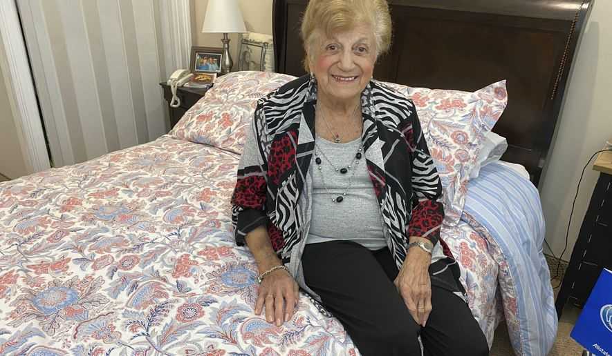 """COVID-19 survivor Anna Fortunato poses for a portrait in her room at The Arbors assisted living community in Jericho, N.Y. on Tuesday, March 31, 2020. Fortunato, 90, says people should keep fighting the new coronavirus and that, """"If I did it, you can do it.""""  For most people, the virus causes mild or moderate symptoms, such as fever and cough that clear up in two to three weeks. For some, especially older adults and people with existing health problems, it can cause more severe illness, including pneumonia and death. (AP Photo/Gabriella Bruzzese)"""
