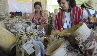 FILE - In this July 11, 2015, file photo, indigenous artisans, who are part of the weaving network Crafts Kalimantan, organize their wares during the 12th annual International Folk Art Market in Santa Fe, N.M. Artists and artisans from more than 50 nations will lose a key source of income and engagement after the International Folk Art Market canceled its annual open-air bazaar in New Mexico due the coronavirus pandemic, event organizers said Tuesday, April 7, 2020. (AP Photo/Susan Montoya Bryan, File)