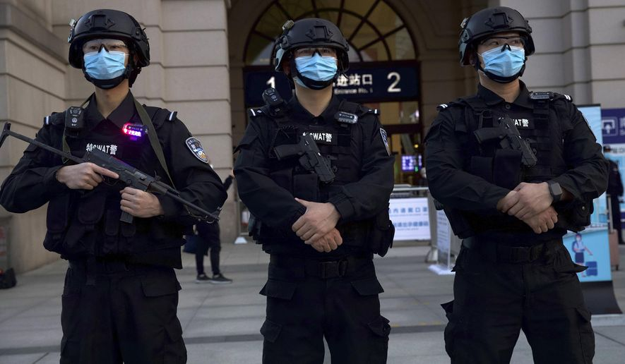 Police officers wearing face masks to protect against the spread of new coronavirus stand guard outside of Hankou train station ahead of the resumption of train services in Wuhan in central China's Hubei Province, Wednesday, April 8, 2020. After 11 weeks of lockdown, the first train departed Wednesday morning from a re-opened Wuhan, the origin point for the coronavirus pandemic, as residents once again were allowed to travel in and out of the sprawling central Chinese city. (AP Photo/Ng Han Guan)