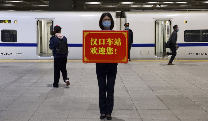 """A railway worker holds a sign reading """"Hankou Station welcomes you!"""" as passengers board the first high-speed train to leave Hankou train station after the resumption of train services in Wuhan in central China's Hubei Province, Wednesday, April 8, 2020. After 11 weeks of lockdown, the first train departed Wednesday morning from a re-opened Wuhan, the origin point for the coronavirus pandemic, as residents once again were allowed to travel in and out of the sprawling central Chinese city. (AP Photo/Ng Han Guan)"""