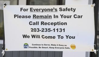 A sign placed in front of the entrance to the Meriden Animal Hospital advises the public of new instructions due to the COVID-19 pandemic, Monday, April 6, 2020. (Dave Zajac/Record-Journal via AP)
