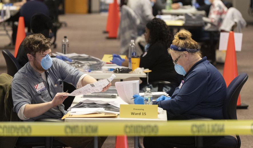 City of Milwaukee Election Commission workers process absentee ballots in Wisconsin's presidential primary election, Tuesday, April 7, 2020, in Milwaukee, Wis. (Mark Hoffman/Milwaukee Journal-Sentinel via AP)