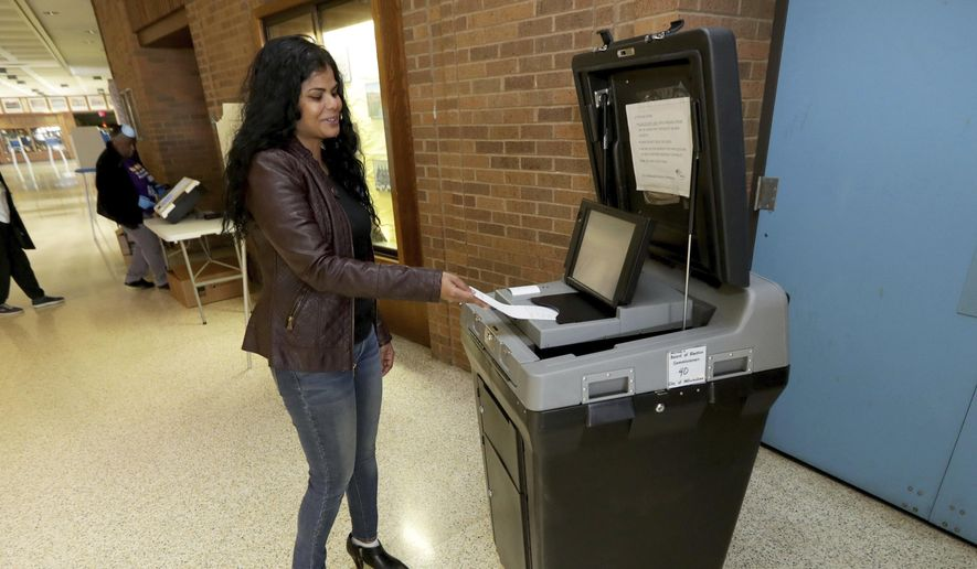 Molly King, an election team member, tests an express voting machine at South Division High School in Milwaukee on Monday, April 6, 2020. Thousands of poll workers had said they wouldn't work, leading Milwaukee to reduce its planned number of polling sites from 180 to just five. More than 2,500 National Guard troops were dispatched to staff the polls. (Mike De Sisti/Milwaukee Journal-Sentinel via AP)