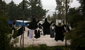 Clothes are hung on the fence of a migrant facility at Malakasa village, north of Athens, Sunday, April 5, 2020. Greece has put the facility outside Athens on lockdown for 14 days after a 53-year-old Afghan developed coronavirus symptoms Saturday afternoon. The new coronavirus causes mild or moderate symptoms for most people, but for some, especially older adults and people with existing health problems, it can cause more severe illness or death. (AP Photo/Yorgos Karahalis)